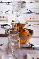 Le Bistrot des Alpilles restaurant. Table with white table cloth and glasses and bread in a basket, knifes forks, spoons. Saint Remy Rémy de Provence, Bouches du Rhone, France, Europe
