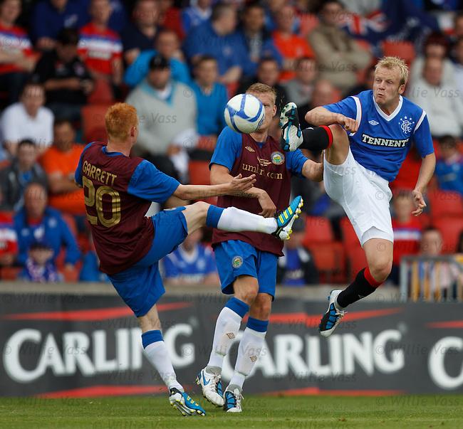 Steven Naismith kung-fu kicks the ball away from Linfield duo Robert Garrett and David Armstrong