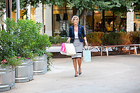 Attractive female shopper accomplishes a busy day of shopping at an Austin outdoor shopping center