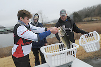NWA Democrat-Gazette/FLIP PUTTHOFF <br /> Luke Carter (from left) and Drew Miller, students at Rogers High School, weigh their bass Jan. 14 2017 with Chris Johnson during the high school bass tournament at Beaver Lake. Carter weighs the duo's big bass at 4.92 pounds. Forty-four area students are on high school fishing teams, said Luci Johnson, director of the program.