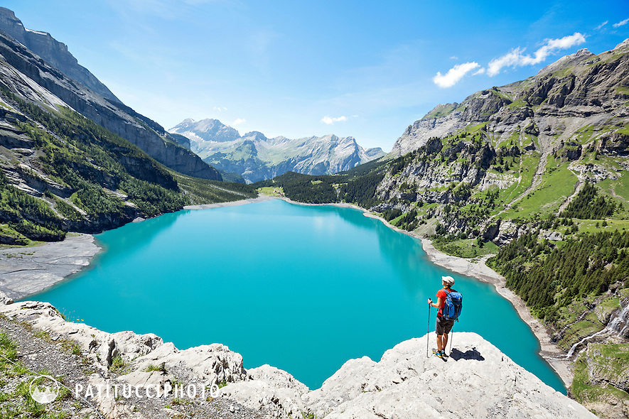 One woman hiking around the turquoise lake of the Oeschinensee, above Kandersteg, Switzerland. The round the lake trail is a very exposed path with cables in many places to hold on to.