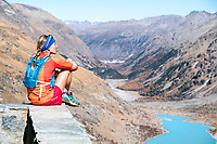 A trail runner sits on the deck of the Chamanna Coaz (Coaz Hut) looking out on the Rosegtal, Pontresina, Switzerland.