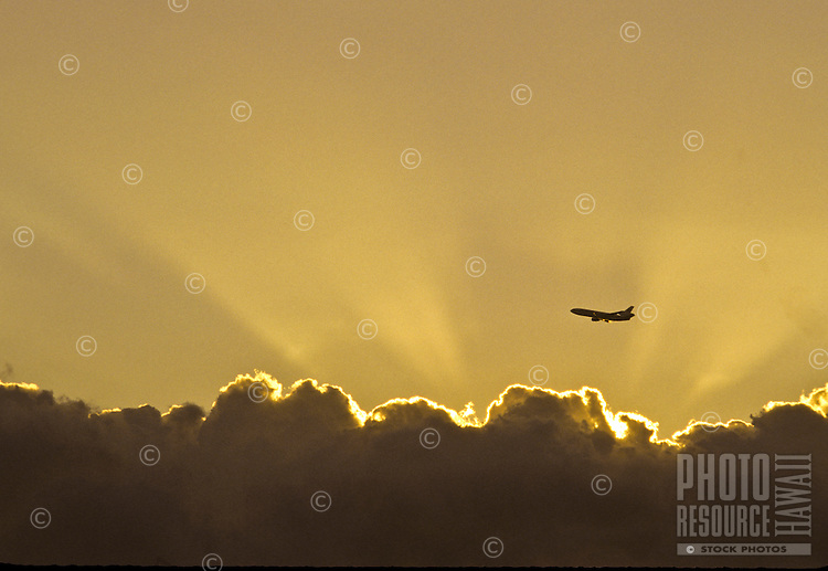 Airplane passing near cloud formation with sun rays