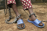 15 year old Alpha has two chains on his feet, one of them chained to a chair which he carries with him for 24 hours a day.  He is detained in the 'City of Rest', a rudimentary counselling and mini rehabilitation centre for recovering drug addicts, alcoholics and traumatised or delinquent youths.  It is run by a pastor who attributes the centre's success to the extensive rest, food and prayer. © Fredrik Naumann Freetown, Sierra Leone.