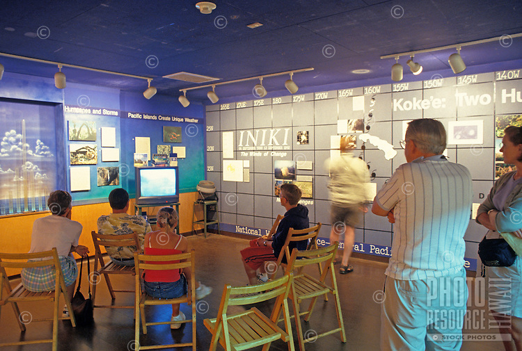 Tourists view a video and exhibits at Kokee Museum on Kauai.  The museum's attractions include scientific and cultural exhibits, craft demonstrations, and a gift shop