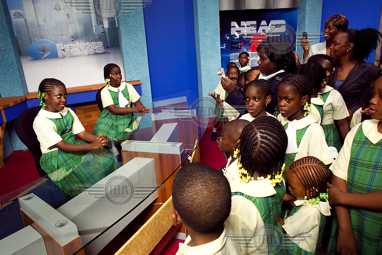 Two girls, part of a visiting school group, pose for pictures in the news presenter's chairs at the privately owned Silverbird TV network.