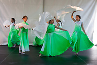 Girls wearing green dresses dancing Chinese Moon Fan Dance, Northwest Folklife Festival 2016, Seattle Center, Washington, USA.