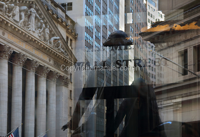 Reflections in a glass window on Wall St, Lower Manhattan, New York, New York, USA, including the New York Stock Exchange, designed by George B Post in Neoclassical style, and built in 1903, at 11 Wall St, and the bronze statue of George Washington, 1882, by John Quincy Adams Ward, outside Federal Hall National Monument. The facade of the NYSE features 2 square corner pillars and 6 columns with Corinthian capitals. The pediment features a sculptural scene by John Quincy Adams Ward entitled Integrity Protecting the Works of Man. Picture by Manuel Cohen