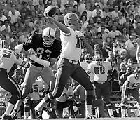 Denver quarterback Don Horn, chased by Raiders Ben Davidson, (1973 photo/Ron Riesterer)