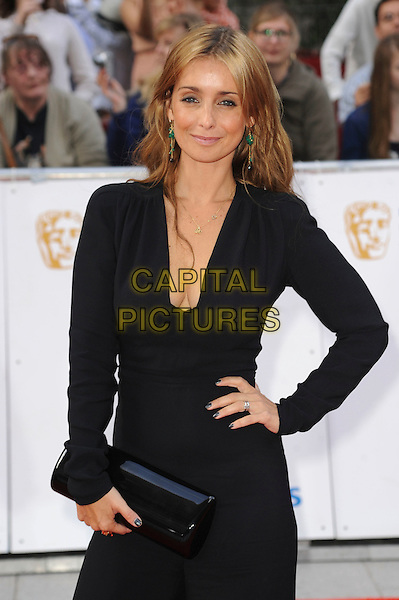 LOUISE REDKNAPP.Attending the Philips British Academy Television Awards, Grosvenor house Hotel, Park Lane, London, England, UK, May 22nd 2011..arrivals TV Baftas Bafta half length black catsuit low cut cleavage clutch bag long sleeve  plunging neckline  hand on hip .CAP/WIZ.© Wizard/Capital Pictures.