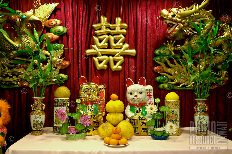 Colorful ceramic cats, vases,ornaments and fruits are displayed as tokens of good luck at a Chinese restaurant in Chinatown. Located near downtown Honolulu, Oahu.