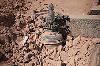 A destroyed artefact lays in the ground of the Shoyembho temple, just outside Kathmandu, Nepal