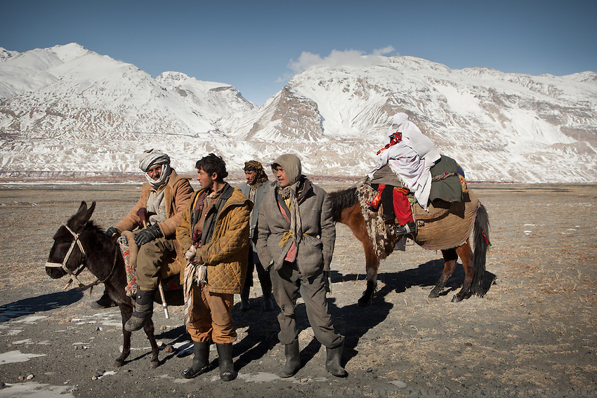 Wakhi people traveling with a donkey and a horse. The woman is hidden under a white Burqa. Driving up from Ishkashim town to Sarhad village, the end of the road in the Wakhan corridor.