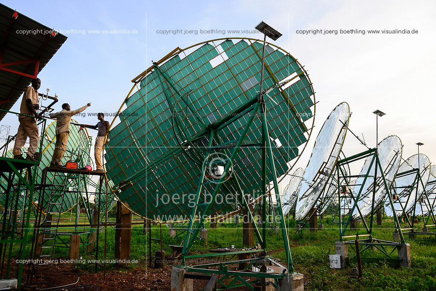 BURKINA FASO, Dano, foundation Dreyer, rice mill with solar cooker, steam is produced by parabolic mirror to process paddy, skilled worker working at water pipe system / BURKINA FASO, Dano, Stiftung Dreyer, Reismuehle mit Solaranlage mit Parabolspiegeln zur Dampferzeugung fuer Reisverarbeitung, Facharbeiter bei Arbeiten am Wasserrohrsystem