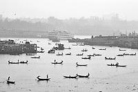 Bangladeshis on country boats cross the Buriganga River in Dhaka, Bangladesh.