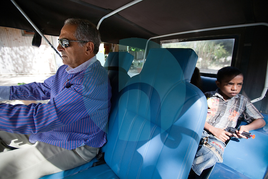 Jose Ramos- Horta, East Timor's president and Nobel Peace Prize winner drives his own car, to ferry two children home, one of them playing with a toy gun, in Dili, Timor-Leste on Sunday, Oct. 23rd, 2011.  Photographer: Daniel J. Groshong/The Hummingfish Foundation