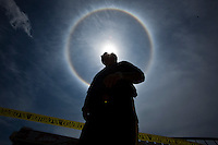 "A police officer stands guard during an atmospheric phenomenon known as a ""sun dog"" while a crane works to remove remnants of the Jet Star roller coaster that had been left in the ocean after Superstorm Sandy hit Seaside Heights last year, in New Jersey  May 14, 2013, Photo by Eduardo Munoz Alvarez / VIEWpress."