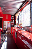 In the kitchen the colour scheme of bright red lacquer and grey ensures a cheerful atmosphere on the dullest Parisian day