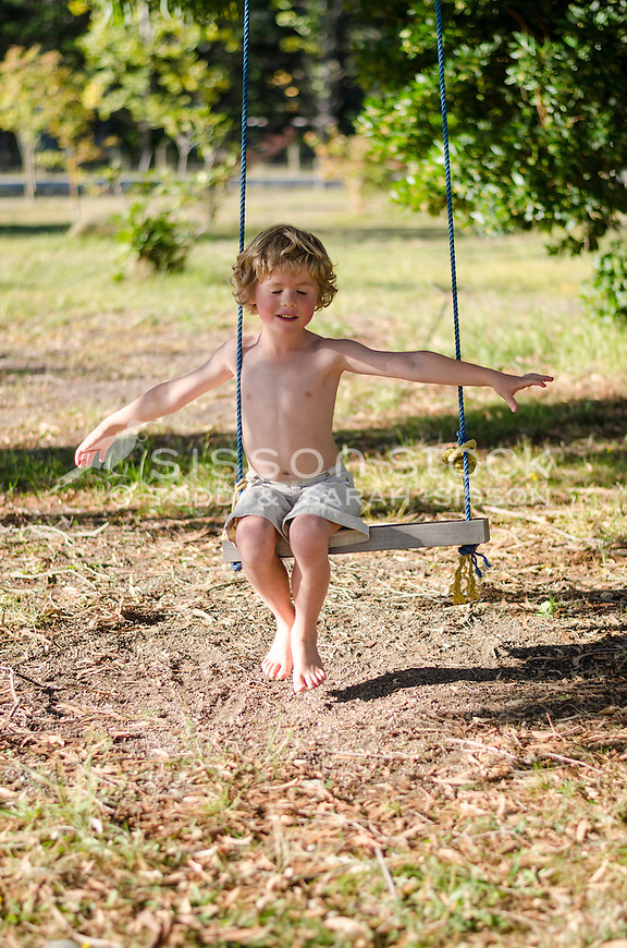 Young boy smiling and sitting on  a rope swing on a summers day, New Zealand - stock photo, canvas, fine art print