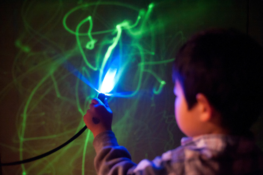 Holden Miller, 3, plays with a UV light wand and draws on a glow-in-the-dark wall at the Madison Children's Museum in Madison, Wis., on Dec. 31, 2010.