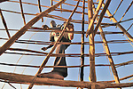 Mawa Santos works on his roof in the Southern Sudan village of Limbe. Santos and his neighbors have returned home from refuge in Uganda to begin rebuilding their war-torn land. NOTE: In July 2011, Southern Sudan became the independent country of South Sudan