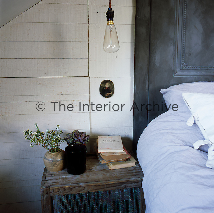 A bare lamp ceiling light hangs above a bedside table, which is made from an old wooden crate. The wall behind is timber clad and painted white.