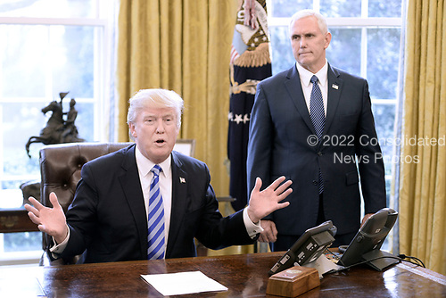 United States President Donald J. Trump reacts after Republicans abruptly pulled their health care bill from the House floor on Friday in the Oval Office of  the White House on March 24, 2017 in Washington, DC.  Standing with the President is US Vice President Mike Pence.<br /> Credit: Olivier Douliery / Pool via CNP