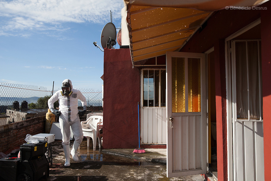 "Donovan wearing his Hazmat suit in front of the scene of an unsolved homicide in Cuernavaca, Morelos – one of Mexico's most dangerous cities on August 7, 2015. The 66-year-old victim was a retired economics lecturer from the local university, and was killed in January of this year. The cleanup took place eight months later. The victim's family has since moved away to avoid further trouble. They remarked that justice is slow in Mexico and expressed dissatisfaction with the police investigation, but appreciated Donovan's discretion and professionalism. Donovan Tavera, 43, is the director of ""Limpieza Forense México"", the country's first and so far the only government-accredited forensic cleaning company. Since 2000, Tavera, a self-taught forensic technician, and his family have offered services to clean up homicides, unattended death, suicides, the homes of compulsive hoarders and houses destroyed by fire or flooding. Despite rising violence that has left 70,000 people dead and 23,000 disappeared since 2006, Mexico has only one certified forensic cleaner. As a consequence, the biological hazards associated with crime scenes are going unchecked all around the country. Photo by Bénédicte Desrus"