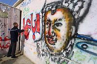 "Amar Abed draws a graffiti mural of Arafat and writes ""every body is Abu Amar"", Abu Amar was Arafat's war name, in the streets of Khan Yunis, in the Gaza Strip. Photo by Quique Kierszenbaum"