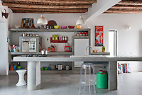 The kitchen has a central island unit and shelving constructed from traditional tadelakt plaster. The beamed ceiling gives the room a rustic feel whilst modern elements are integrated into the design. Beside the central unit is a Tam Tam stool and a Philippe Starck Charles Ghost stool.