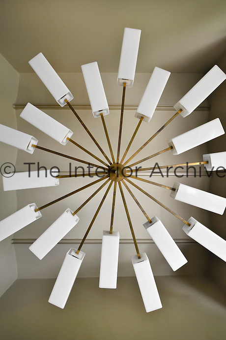 A view looking up to a contemporary light fitting hanging from the ceiling.