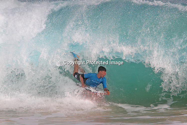 A boarder drops in a curl at Sandy Beach in Hawaii during high-tide.