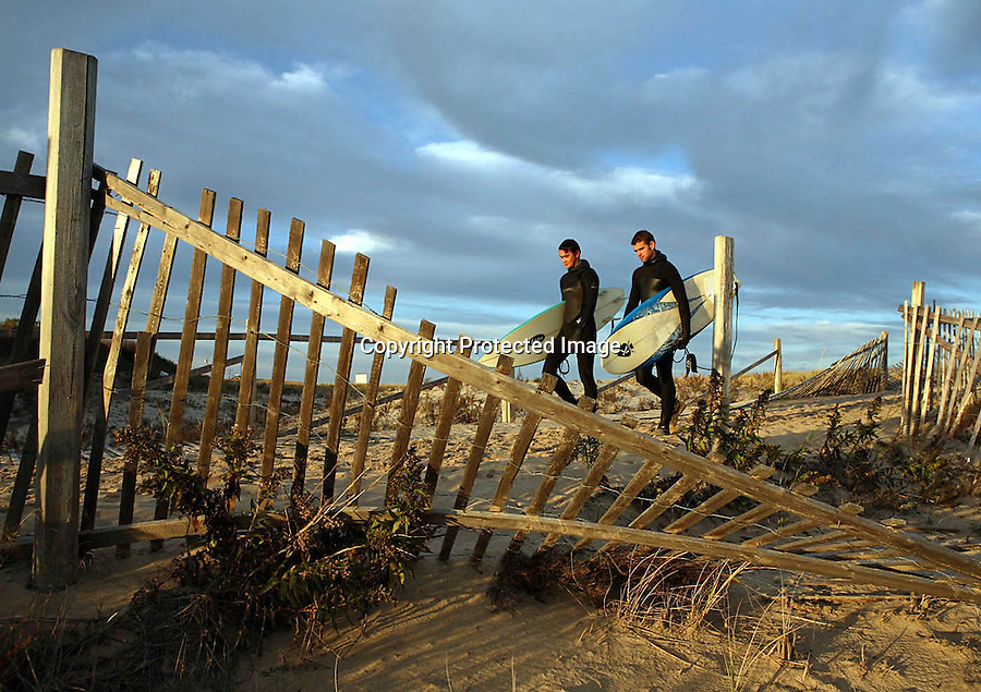 Two surfers walk past snow fences damaged by yesterday's storm at Nauset Beach in Orleans, MA.  The storm swell brought many surfers out to Cape Cod's beaches today.