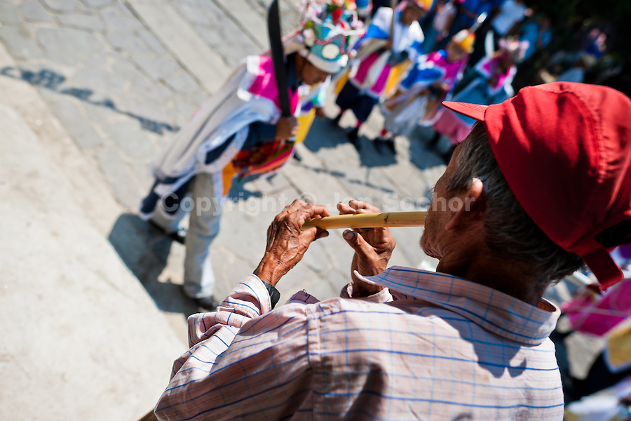 "A Salvadoran man plays flute during the procession of the Flower & Palm Festival in Panchimalco, El Salvador, 8 May 2011. On the first Sunday of May, the small town of Panchimalco, lying close to San Salvador, celebrates its two patron saints with a spectacular festivity, known as ""Fiesta de las Flores y Palmas"". The origin of this event comes from pre-Columbian Maya culture and used to commemorate the start of the rainy season. Women strip the palm branches and skewer flower blooms on them to create large colorful decoration. In the afternoon procession, lead by a male dance group performing a religious dance-drama inspired by the Spanish Reconquest, large altars adorned with flowers are slowly carried by women, dressed in typical costumes, through the steep streets of the town."