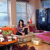 Portrait of designer Suzanne Boyd sitting on the sofa in her living room