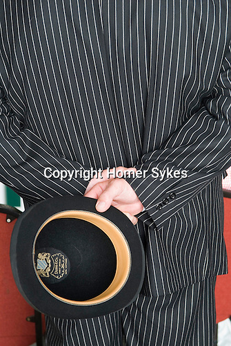 Festival of Hunting Peterborough Uk. Man dressed in dress code dark stripped suit and carrying his bowler hat watches a hound show. 2013