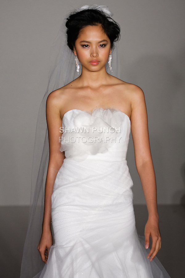 Model walks runway in a Rae wedding dress - Pearl white organza fit-to-flare gown with tulle overlay and blooming petaled bodice, by Hayley Paige, for the Hayley Paige Spring 2012 Bridal collection, at the JLM Couture fashion show, during Bridal Week New York Spring 2012.