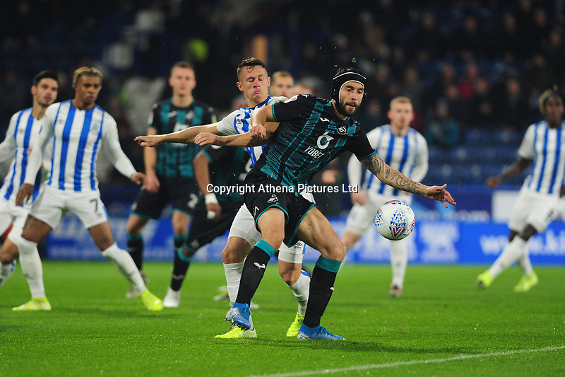 Jonathan Hogg of Huddersfield Town vies for possession with Borja Baston of Swansea City during the Sky Bet Championship match between Huddersfield Town and Swansea City at The John Smith's Stadium in Huddersfield, England, UK. Tuesday 26 November 2019