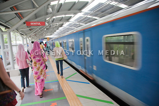 Women dressed in traditional Malay clothing boarding at Sentul Station (KTM Komuter train station). Selangor, Malaysia