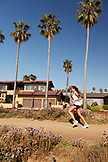 USA, California, San Diego, a young woman jogs along a dirt path near Ocean Beach