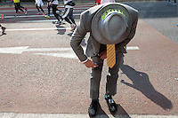 A runner in a suit applies pain-killing spray to tired muscles during the 10th Tokyo Marathon took place on a fine spring day in Tokyo Japan. Sunday February 28th 2016. Thirty-six thousand runners took part with Ethiopian,  Feyisa Lilesa winning the  men's competition and  Kenyan, Helah Kiprop victorious in the women's race.