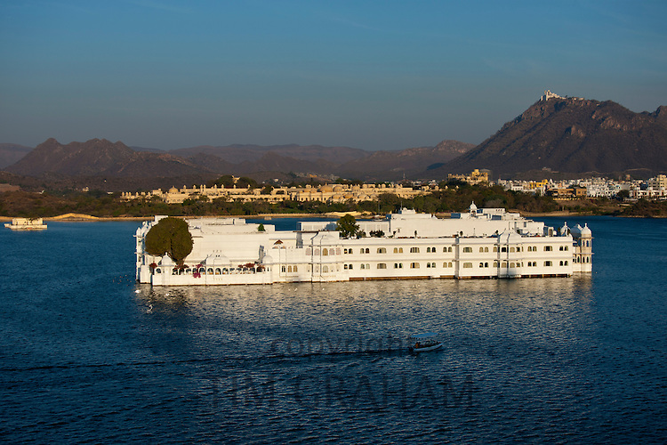 Lake Palace Hotel, Jag Niwas, on island site on Lake Pichola in early morning with boat leaving, Udaipur, Rajasthan, India