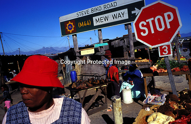ditown00285.Digital. Townships. Women selling cow intestines, sheep heads in Town 2 on November 8, 2003 in Site B Khayelitsha township. It's popular for making traditional food.  Lifestyle, poverty, road signs, trade,  stalls, red hat. .©Per-Anders Pettersson/iAfrika Photos