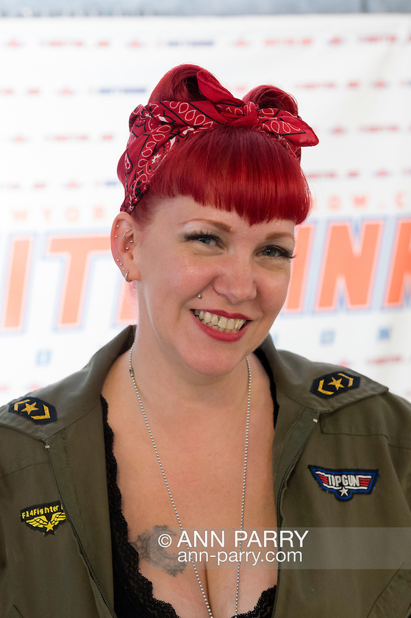 Garden City, New York, USA. September 13, 2015. FRANKEY REDD, of Glen Cove, poses at the Instagram booth at the United Ink Flight 915 Tattoo convention at the Cradle of Aviation Museum in Long Island. Redd is dressed like a WWII Rosie the Riveter pinup girl, with her red hair tied up in a red and white bandana.