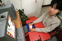 Li Yan operates her computer with the sole four fingers that she can move, in her home in Yinchuan, Ningxia Province, China, on May 7, 2007. Li Yan spends up to 10 hours per day in front of her computer, producing colourful paintings and writing her blog. 28-year-old Li Yan suffers from motor neuron disease also known as amyotrophic lateral sclerosis (or ALS), the same illness that has thereotical physicist Stephen Hawking. Li Yan asked China's National People's Congress (NPC) to consider a draft on euthanasia. Photo by Lucas Schifres/Pictobank