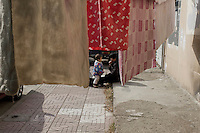 A woman chats with her son as local residents air their quilts on a pedestrian pavement in Nanjing, Jiangsu province, China, November 2012.