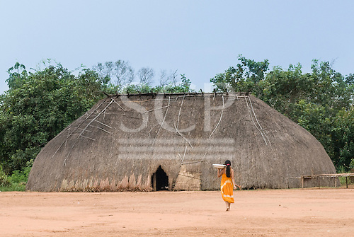 Xingu Indigenous Park, Mato Grosso State, Brazil. Aldeia Afukuri (Kuikuro). Typical oca house with traditional thatch door to right of doorway.