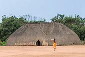Xingu Indigenous Park, Mato Grosso State, Brazil. Aldeia Afukuri (Kuikuro). Typical oca house with traditional thatch door to right of doorway.