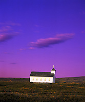 Scenic, moody view of a church on a prairie with yellow flowers growing in the field under a purple sky with clouds. Montana.