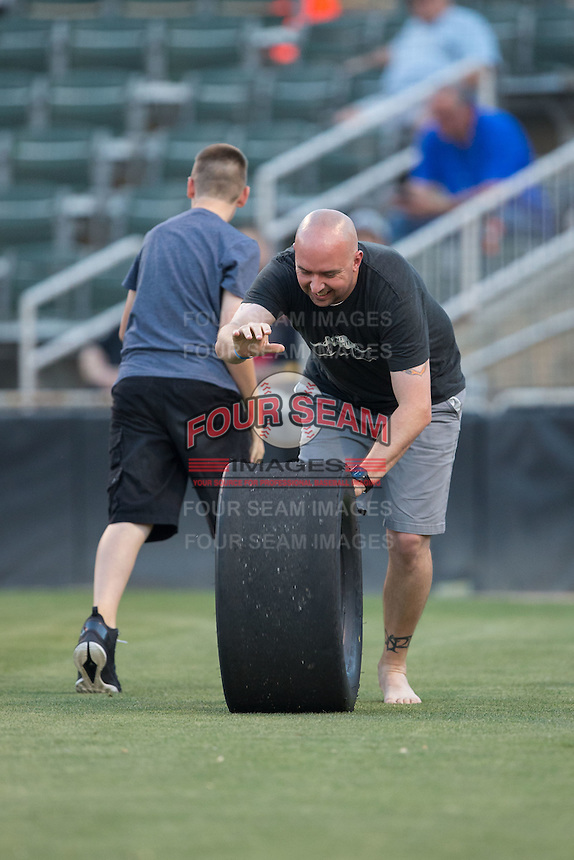 A fan rolls a race car tire during a between innings contest during the South Atlantic League game between the Asheville Tourists and the Kannapolis Intimidators at Kannapolis Intimidators Stadium on May 26, 2016 in Kannapolis, North Carolina.  The Tourists defeated the Intimidators 9-6 in 11 innings.  (Brian Westerholt/Four Seam Images)